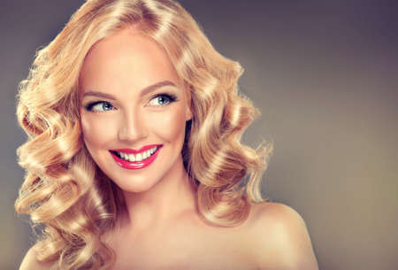 glans: Young wide smiling blonde haired girl-model. Loose, dense,  blond hair, red make up and healthy teeth.