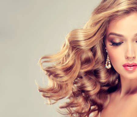 hairdress: Beautiful girl blonde. Hair with an elegant hairstyle, wavy hair , curly hairstyle.  Long,nice eyelashes and big earrings.