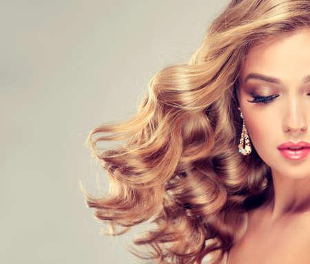 Schöne blonde Mädchen. Haar mit einem eleganten Frisur, gewelltes Haar, lockige Frisur. Lange, schöne Wimpern und große Ohrringe.