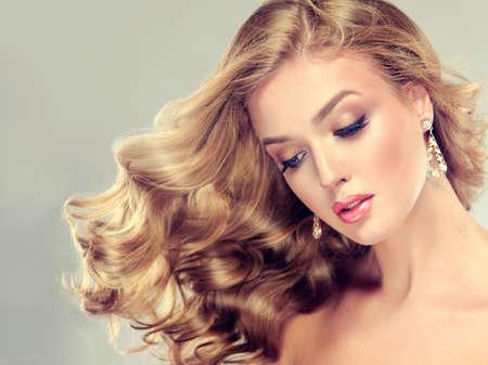 Belle fille blonde. Cheveux avec une coiffure élégante, cheveux ondulés, bouclés coiffure. Long, de beaux cils et les grandes boucles d'oreilles.