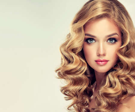 hair treatment: Beautiful girl blonde. Hair with an elegant hairstyle, wavy hair , curly hairstyle .Straight look on camera. Stock Photo