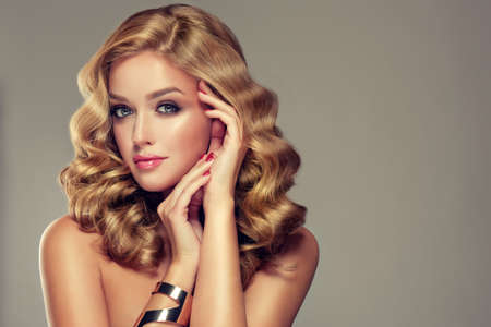 hair treatment: Beautiful girl blonde. Hair with an elegant hairstyle, hair wavy, curly hairstyle . Jewellery, earrings and bracelet. Stock Photo