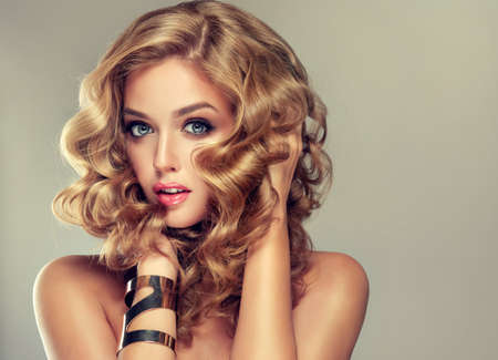 Beautiful girl blonde. Hair with an elegant hairstyle, hair wavy, curly hairstyle . Jewellery, earrings and bracelet. Stock Photo