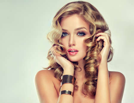 Beautiful girl blonde. Hair with an elegant hairstyle, hair wavy, curly hairstyle . Jewellery, earrings and bracelet. Banco de Imagens