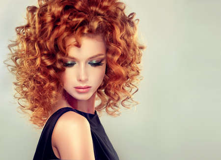 tendrils: Pretty red haired girl with curly hairstyle and elegant make up. Closeup portrait.
