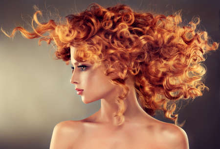 red head girl: Pretty red haired girl with curly hairstyle.Flying hair in dinamic movement.