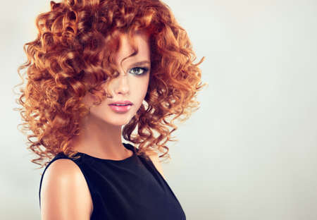 woman hairstyle: Pretty red haired girl with curly hairstyle and elegant make up. Closeup portrait.