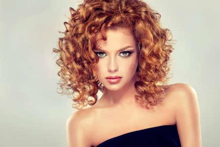 Jolie rouge fille aux cheveux avec des boucles, le maquillage à la mode. Regardez droit devant la caméra.