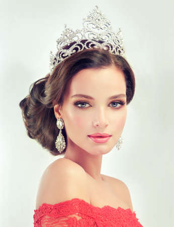 Young, gorgeous model  in a delicate make up, dressed in a red gown and crown on her head. Misty, romantic look. Wedding and evening style. Foto de archivo