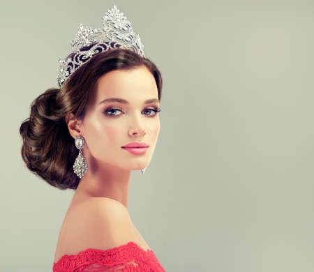 若い、繊細なメイクでゴージャスなモデルは赤いガウンと彼女の頭の上の王冠に身を包んだ。霧、ロマンチックな一見。結婚式や夜のスタイル。