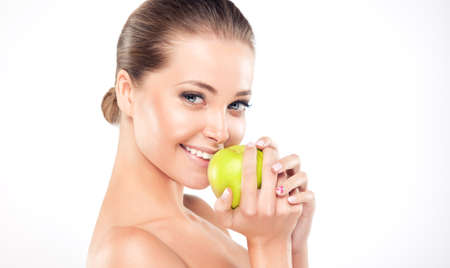 Young,smiling girl  holds a green apple. Cosmetic, cosmetology and stomatology. Banco de Imagens