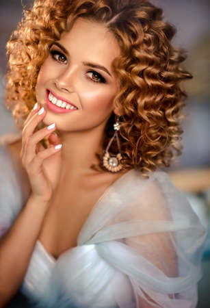 Nice smiling young girl model with dense, curly hair, dressed in evening gown and big earings. Banco de Imagens