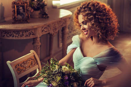 Nice smiling young girl model with dense, curly hair, dressed in evening gown and big earings. Portrait in classical interior.