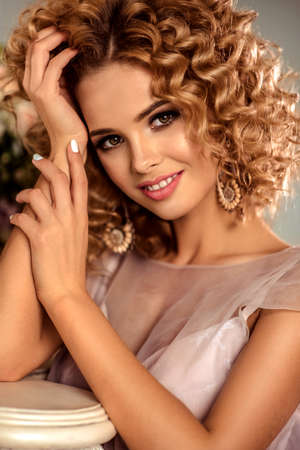 pretty hair: Nice smiling young girl model with dense, curly hair, dressed in evening gown and big earings. Stock Photo