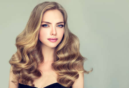 Young girl model with blue eyes and dense, curled, healthy hair. Example of long hairstyle.