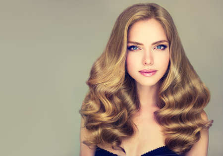 Modelo de la chica joven con los ojos azules y denso, rizado, el pelo sano. Ejemplo de corte de pelo largo.