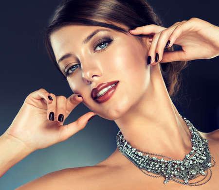labios sensuales: Primer plano retrato de joven modelo agradable, con grandes collares. estilo elegante, manicura negro brillante y maquillaje.