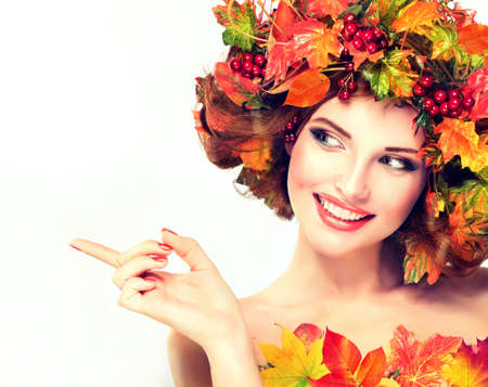 Autumn Beauty. Red and yellow autumn leaves and red berry in wreath on girl head. Archivio Fotografico