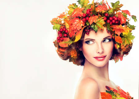 Autumn Beauty. Red and yellow autumn leaves and red berry in wreath on girl head. Banco de Imagens