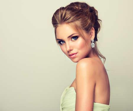 aretes: Joven y atractiva rubia modelo, mirada recta en la cámara. peinados de moda, maquillaje y vestuario.