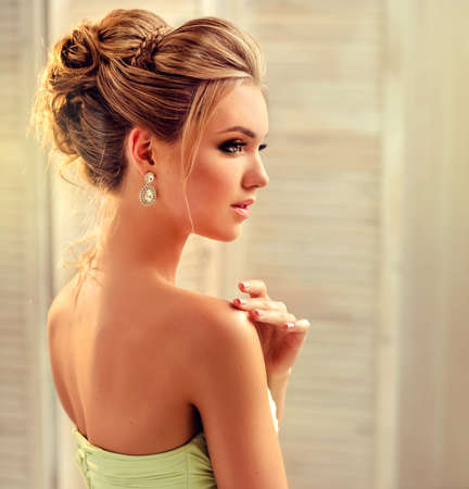 Elegant wedding or evening hairstyle on the head of blond-haired lady.Portrait in profile. Stock Photo