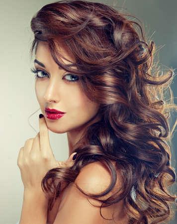 Modell mit dichtem, lockigem Haar. Luxus-Mode-Stil, Maniküre, Kosmetik und Make-up. Standard-Bild - 63353227