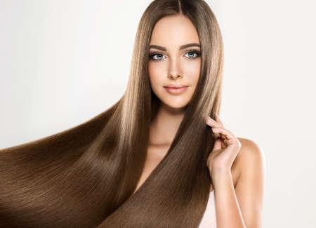 Muchacha atractiva joven modelo con el pelo magnífico, brillante, de largo, recto. Buena y saludable del cabello como resalt de atención adecuada.