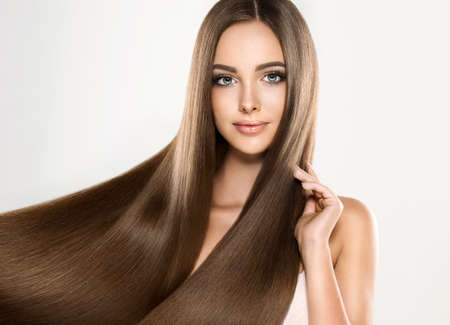 Young attractive girl-model with gorgeous, shiny, long, straight hair. Good and healthy hair as resalt of right care. Stock Photo