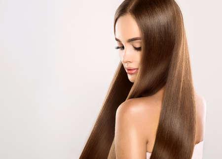 cabello lacio: Muchacha atractiva joven modelo con el pelo magnífico, brillante, de largo, recto. Buena y saludable del cabello como resalt de atención adecuada. Foto de archivo
