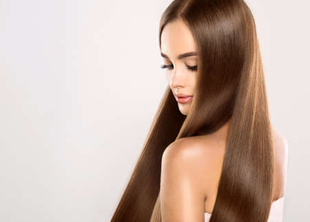 long straight hair: Young attractive girl-model with gorgeous, shiny, long, straight hair. Good and healthy hair as resalt of right care. Stock Photo
