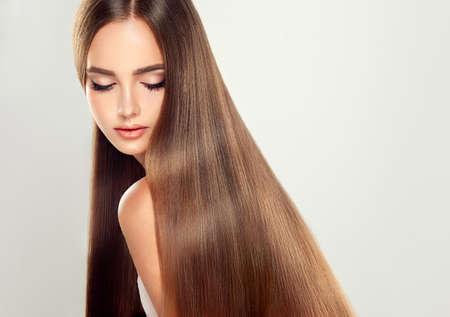 아름다움: 화려한, 빛나는, 긴 직선 갈색 머리를 가진 젊은 매력적인 여자 모델. 권리 보호의 resalt 좋은 건강한 머리.