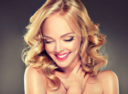 Young wide smiling blonde haired girl-model. Loose, dense, blond hair, red make up and healthy teeth. Banco de Imagens