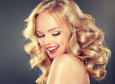 Young wide smiling blonde haired girl-model. Loose, dense, blond hair, red make up and healthy teeth. Stock Photo