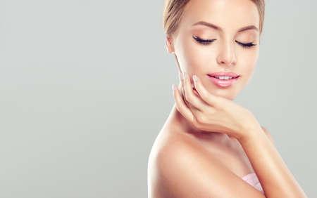 frescura: Retrato de la hermosa joven, sonriendo Mujer con la piel tocando la cara limpia, fresca, propia. Tratamiento facial. Cosmetología, belleza y spa.