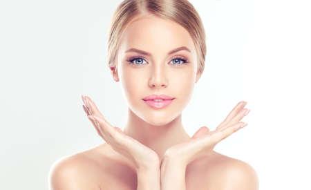 Portret piękna młoda, uśmiechnięta kobieta z czystą skórę, dotykając własnej twarzy. Zabieg na twarz. Kosmetyka, uroda i spa.