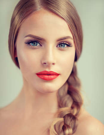 Close up portrait of beautiful young woman with braid(pigtail), bright red lips and blue eyes. Fashion ,beauty and cosmetic. Foto de archivo
