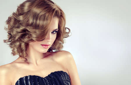 Beautiful model brunette with middle length curled hair and bright make up. Glamour evening style and playful look.