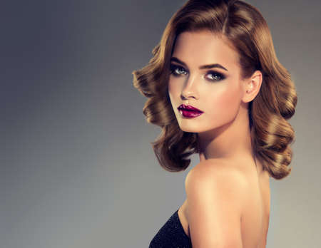 feeling up: Beautiful model brunette with middle length curled hair and bright make up. Glamour evening style. Stock Photo