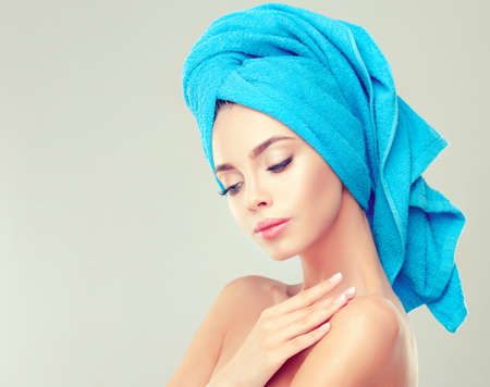 Portrait of young woman with clean fresh skin and soft, delicate make up,with towel on her head.Image of freshness and cleanliness.