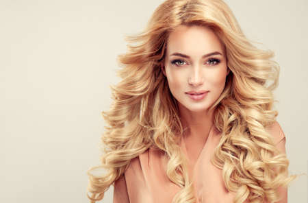 Attractive woman blonde with elegant hairstyle. Example of long,dense and curly hair. Banco de Imagens