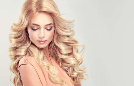 Attractive woman blonde with elegant hairstyle. Example of long,dense and curly hair. Foto de archivo