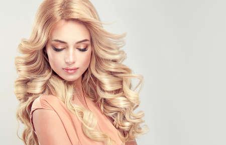 Séduisante femme blonde avec une coiffure élégante. Exemple de cheveux longs, denses et bouclés. Banque d'images - 71573685