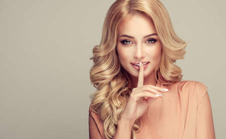 Attractive woman blonde with elegant hairstyle holds finger in front her lips. Lady with a secret.