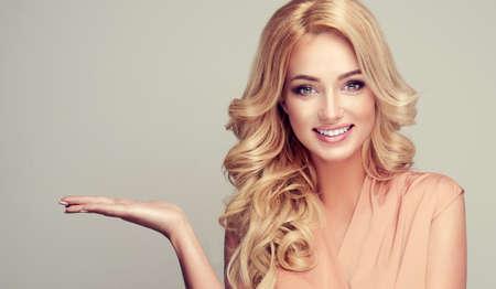 Atrakcyjna blondynka kobieta z szerokim uśmiechem i wskazuje na bok i przedstawia swój produkt.