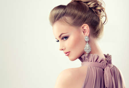 Portrait of young gorgeous girl dressed in evening gown,with delicate makeup on her face and large jewelry earrings on ears. Example of evening or wedding hairdress.