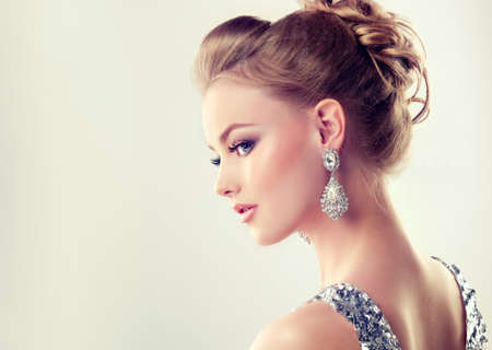 Portrait of young gorgeous girl in a profile  dressed in evening gown,with delicate makeup on her face and large jewelry earrings on ears. Evening or wedding hairdress and style.