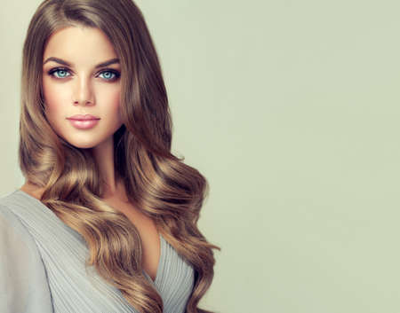 Long haired, appealing  model with dense, curled, well cared hair. Portrait of gorgeous young woman with elegant make up and perfect hairstyle.