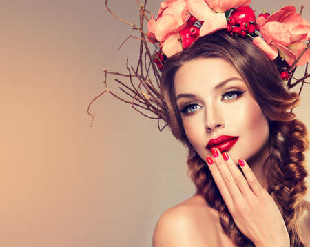 Girl with delicate wreath from flowers, fruits and twigs on her head. Hair braided in thick pigtails, vivid make-up and bright-red lipstick on the lips. Stok Fotoğraf