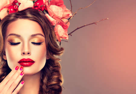 Girl with delicate wreath from flowers, fruits and twigs on her head. Hair braided in thick pigtails, vivid make-up and bright-red lipstick on the lips. Banco de Imagens