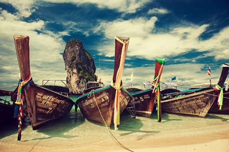 Thailand. Krabi province. Boats decorated by bright cloth  is moored in a turquoise lagoon of Phra Nang beach. Big not inhabited rock, blue and cloudy sky on the background. Editorial